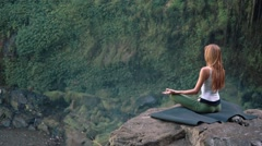 Young woman practicing yoga lotus pose on the edge of a cliff next to Tegenungan Stock Footage