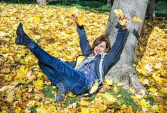 Crazy young woman throwing yellow leaves in autumn, seasonal lifestyle Stock Photos