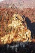 The rock in autumn forest by sunset in Harmanec, Slovakia, natural scene Stock Photos