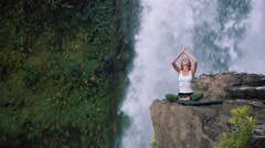 Woman raising hands in yoga lotus pose on the edge next to Tegenungan Waterfall Stock Footage