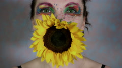 4k Shot of a Woman with Multicoloured Make-up With Sunflower (focus on face) Stock Footage