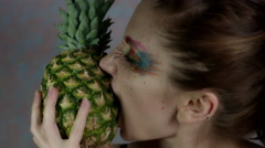 4k Shot of a Woman with Multicoloured Make-up Biting Pineapple Stock Footage