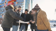 Young designers stand on street and discuss plan of construction Stock Footage