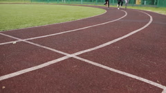 Athletes, mans and womans running on running track Stock Footage