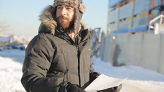 Bearded man stands on cold winter street and keeps plan in his arms Stock Footage