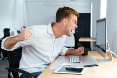 Aggressive furious businessman shouting and working with computer in office Stock Photos