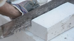 Worker cutting lightweight concrete block used for construction with saw Stock Footage