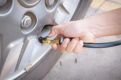 Filling air into a car tire Stock Photos