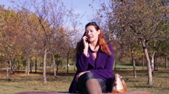 Woman Talking by Phone in Autumn Park Stock Footage