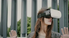 Brunette woman girl uses virtual reality glasses in the urban space Stock Footage