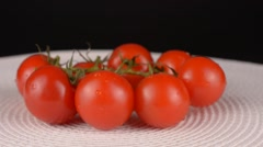 Close up of cherry tomatoes on black background Stock Footage