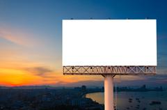 Blank billboard ready for advertisement in city downtown with sunrise backgro - stock photo