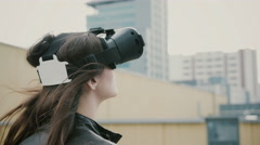 Brunette woman girl with waving hair uses 3D Virtual Reality headset on the roof Stock Footage
