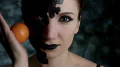 4k Shot of a Woman with Halloween Make-up Rolling an Orange on Face Stock Footage
