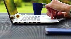 Middle aged woman is working on laptop sitting in beautiful garden Stock Footage