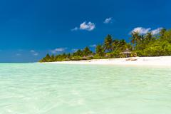 Padaraise tourist beach with white sand, palm trees and sun loungers Stock Photos