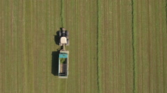 AERIAL: Farmer in tractor working on farm field and collecting fodder in swaths Stock Footage