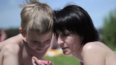 Mom and son at a beach playing with a smartphone Stock Footage