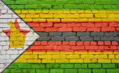 Flag of Zimbabwe painted on brick wall, background texture Stock Photos