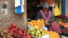 A woman bags fresh mandarins at a market in cuzco, peru Stock Footage