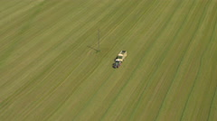 AERIAL: Farmer in tractors working on farm field picking up hay near small town Stock Footage