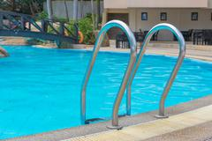 blue swimming pool at hotel with stair - stock photo