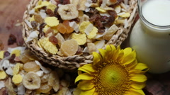 Cereal, dried fruit and jug of milk on wooden table, rotating Stock Footage