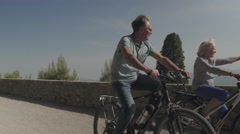Senior couple cycling on electric bicycles Stock Footage