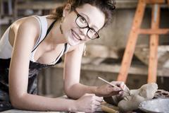 Young artist moulding raw clay in art studio Stock Photos