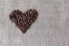 Burlap texture with coffee beans heart shape Stock Photos