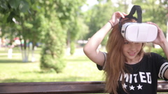 Handsome girl looking in virtual reality goggles sitting in park, outdoors - stock footage