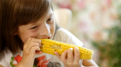 Little girl eats a boiled corn Stock Footage