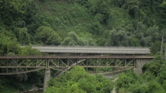 Train Passing Between Mountains And Forest Stock Footage