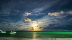 Moonrise breaks through the clouds over the sea on the beach of Nusa Dua. 4K - stock footage