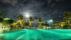 Illuminated night pool against the backdrop of palm trees and the sea. 4K Stock Footage