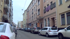 Many Cars Parked on a City Street. Buildings, Road, Passing One Car Arkistovideo