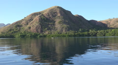 4k Mountain island mirroring in Flores Sea while shipping Stock Footage