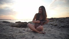 Happy young female in bikini sitting on beach and playing ukulele slow motion Stock Footage