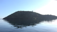 4k Mountain island mirroring in calm Flores Sea while shipping Stock Footage