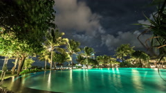 Clouds float above the illuminated night pool against the backdrop of palm trees - stock footage