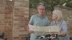 Senior couple looking at map on holiday - stock footage
