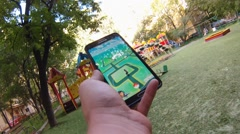 Pokemon Go app being played by a man on his mobile phone while walking on garden Arkistovideo
