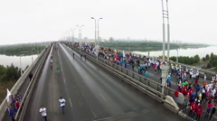 Young people run a marathon on a large bridge across the river Stock Footage
