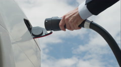CLOSE UP: Businessman plugging out white electric car at charging station Stock Footage