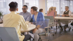 4K Happy professional group drinking coffee & chatting in office breakout area Stock Footage