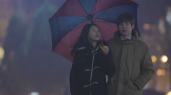 Teenagers having first date, couple walking in park with umbrella, relaxation Stock Footage