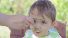 A child sitting at the children's table. Mom feeding the baby cereal Stock Footage
