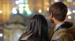 Loving couple kissing and hugging, looking at night city, enjoying romantic date Stock Footage