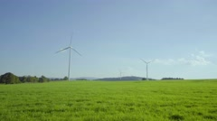 4K UHD Windmill park on grassy field with blue sky Stock Footage