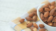 Almonds in brown bowl on wooden background - stock footage